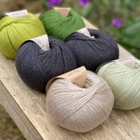 Six balls of yarn in black and greens