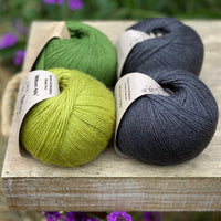 Four balls of yarn in black and greens