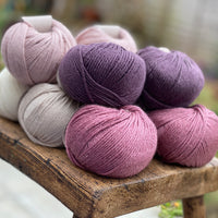 10 balls of yarn in five colours, a fade of pink/purple