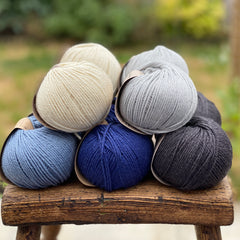 10 balls of yarn in five colours, a fade of blues