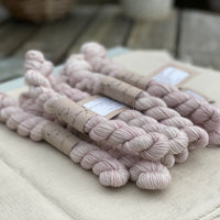 Pale pink mini skeins of yarn with silver sparkle