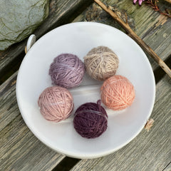 Five small balls of yarn in muted pinks and purple