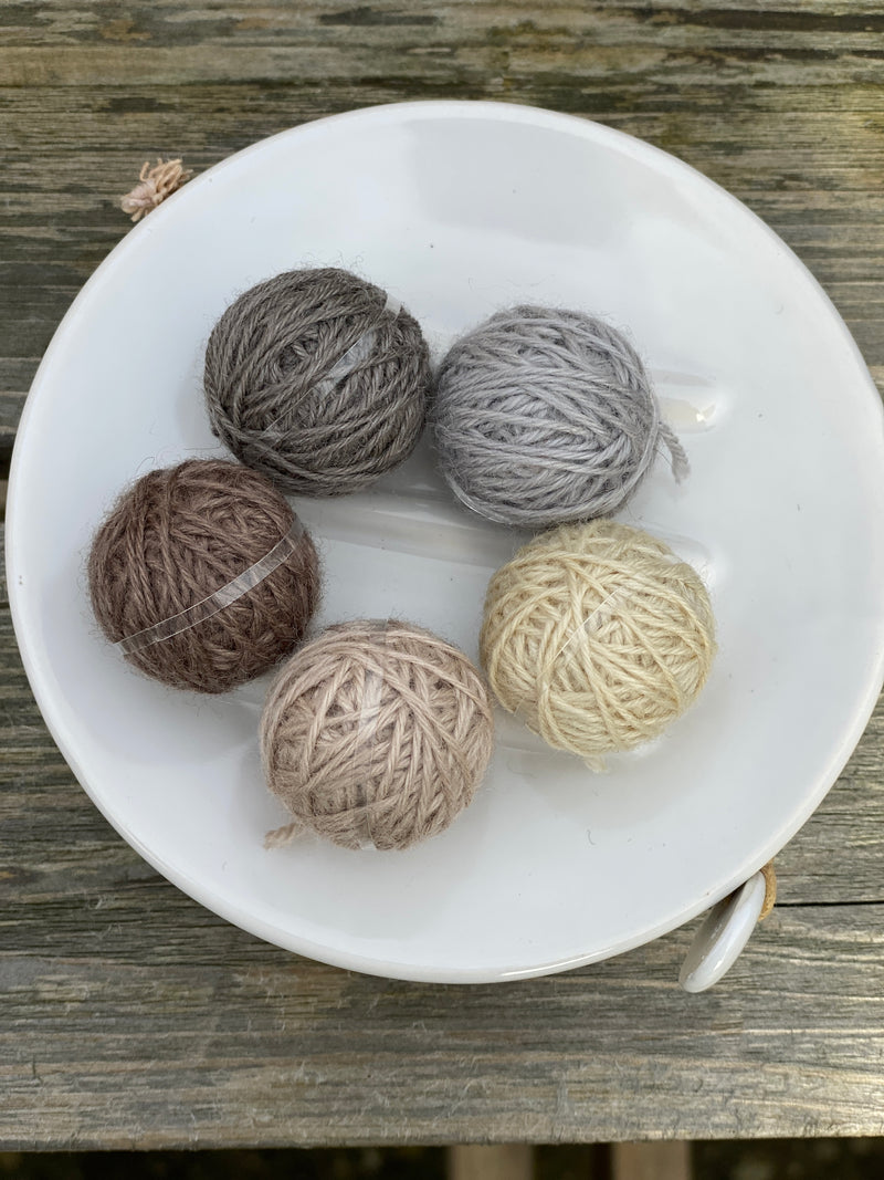 Five small balls of yarn in neutral shades