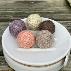 Five small balls of yarn in soft browns, purple and peach