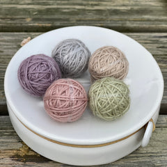 Five small balls of yarn in pastel shades