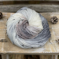Variegated white, grey and brown yarn with black speckles