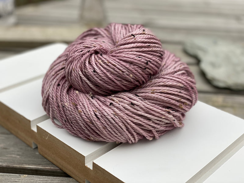 Lilacy pink yarn with black, brown and cream neps running through it.