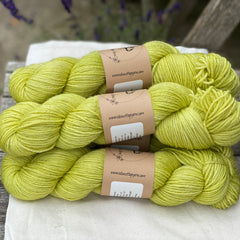 Zingy green skeins of yarn sat on a piece of white fabric on a wooden chair