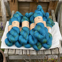 Blue yarn with flashes of green running through the skeins. The yarn is sat on a piece of white fabric on a wooden chair.