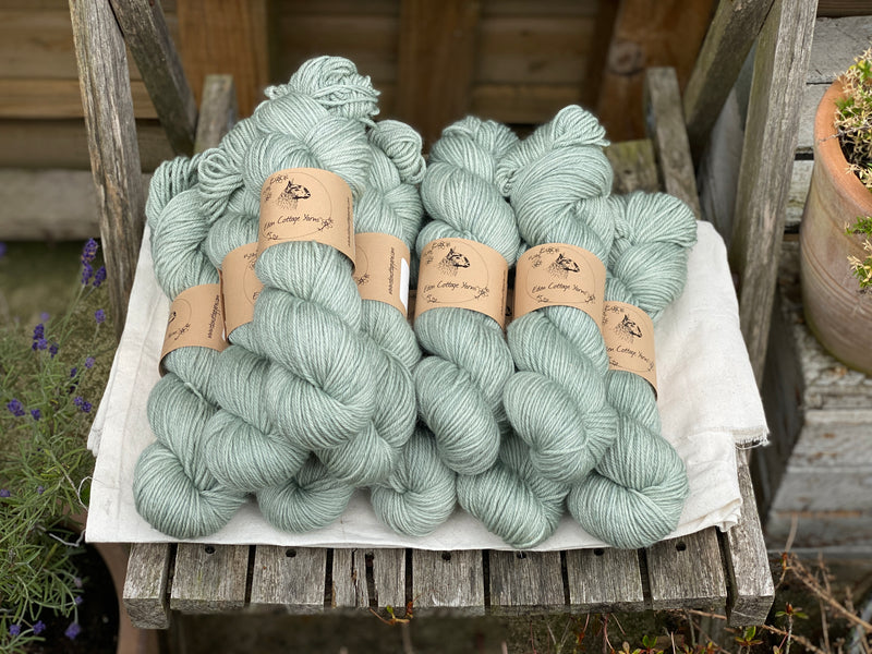 Pale green skeins of yarn sat on a piece of white fabric on a wooden chair