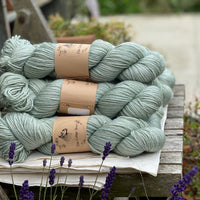 Pale green skeins of yarn sat on a piece of white fabric on a wooden chair. Lavender flowers are visible at the bottom of the image