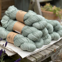 Pale green skeins of yarn sat on a piece of white fabric on a wooden chair. Lavender flowers are visible in the bottom left corner of the image.