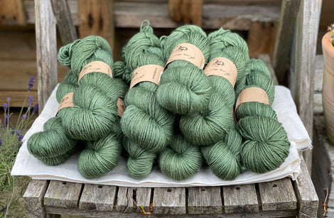 Dark green skeins of yarn sat on a piece of white fabric on a wooden chair