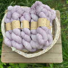 Pale purple yarn in a white wicker basket. The basket is on a wooden stool which sits in long grass.