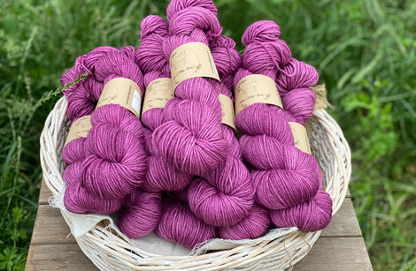 Pinky-purple yarn in a white wicker basket. The basket sits on a wooden stool with a backdrop of grass.
