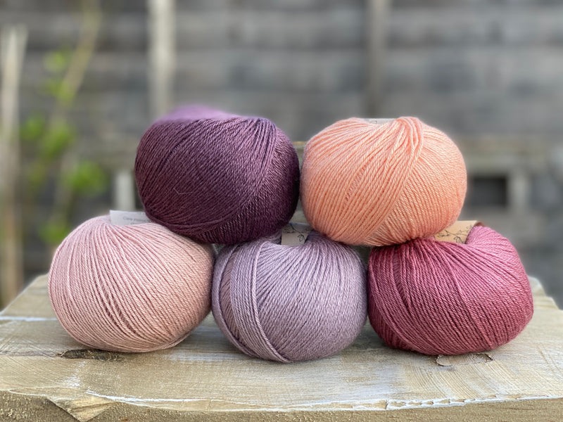 Five balls of yarn in shades of pink and purple