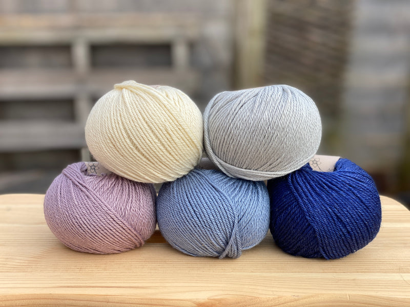Five balls of yarn in shades of blue and purple