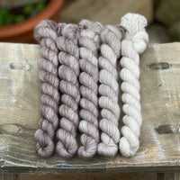 Five mini skeins of yarn fading from mid to light brown