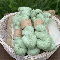 Pale green yarn in a white wicker basket. The basket sits on a wooden stool with a backdrop of grass.