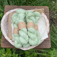 Pale green yarn in a white wicker basket. The basket sits on a wooden stool with a backdrop of grass and green plants.