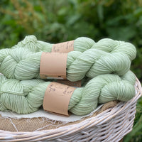 Pale green yarn in a white wicker basket. The backdrop is of green foliage out of focus.