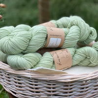 Close up image of pale green yarn showing silver sparkle element of the yarn. The yarn is sat in a white wicker basket.