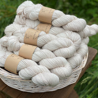 Beige yarn in a white wicker basket. The basket sits on a wooden stool with a backdrop of grass.