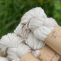 Close up image of beige yarn showing silver sparkle element of the yarn.