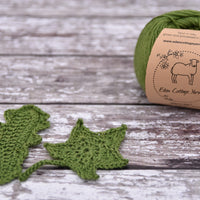 Green yarn alongside crochet leaves