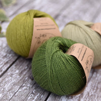 Three balls of green yarn in different shades
