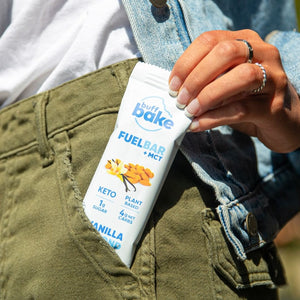 Vanilla Almond protein bar hanging out of a pocket.  These snacks are great for on the go!  Filled with benefits of MCT oil.