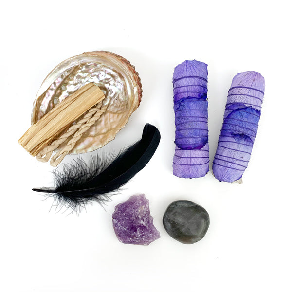 Two Purple Rose Wrapped White Sage Sticks, Abalone Shell, Palo Santo Sticks, Black Feather, Raw Amethyst Stone, And Black Moonstone.