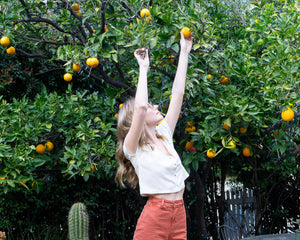 Julia reaching for oranges in her Patti Pants and Reversible Silk Blouse in Beachwood Canyon. Image by The Canyon