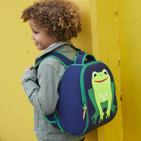 Young boy carrying the Dabbawalla Bags Frog backpack.  Bright green cute frog is stitched on the front of a navy preschooler backpack.