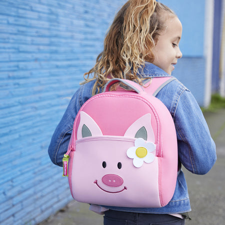 School girl wearing the adorable Pink Piglet  backpack from Dabbawalla Bags.  Light Pink face on a bright pink bag.  Cute daisy over right ear.