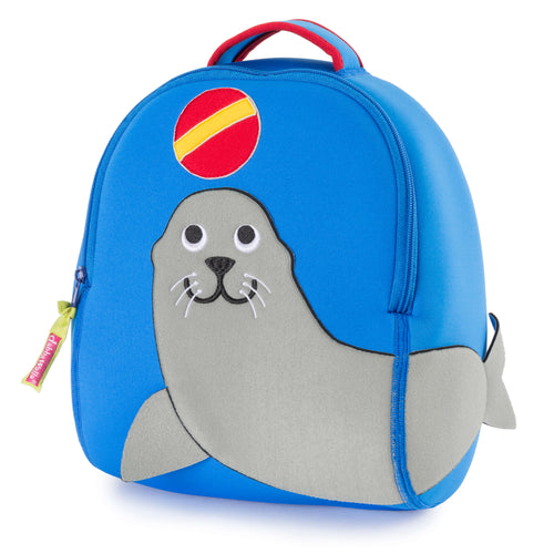 Large happy grey seal lion on front of a marine blue preschool backpack.  Sea lion is playing with a red ball with yellow stripe
