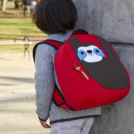 Preschool boy with Sloth Backpack .  Red backpack with brown smiling sloth.