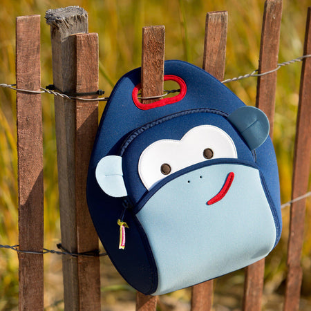 Monkey lunch bag hanging on a fence.