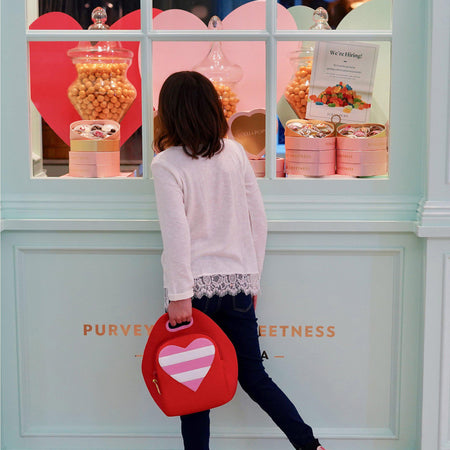 Girl looking in the window of a candy shop.  She is carrying the Heart lunch bag from Dabbawalla Bags.