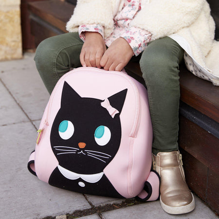 Young girl with close up of Miss Kitty Backpack.  Cute black kitty face is appliqued on the front of a pink bag.