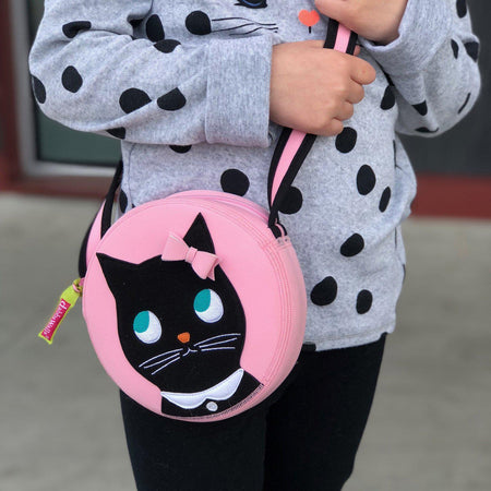 Close-up of the Miss Kitty cross body bag from Dabbawalla Bags.  Pink circle bag has a cute kitty appliqued on the front panel.