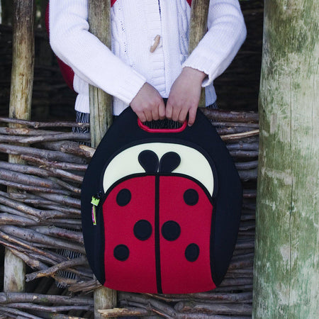Small girl carrying Dabbawalla Bags Cute as a Ladybug insulated lunch Bag while exploring outside.