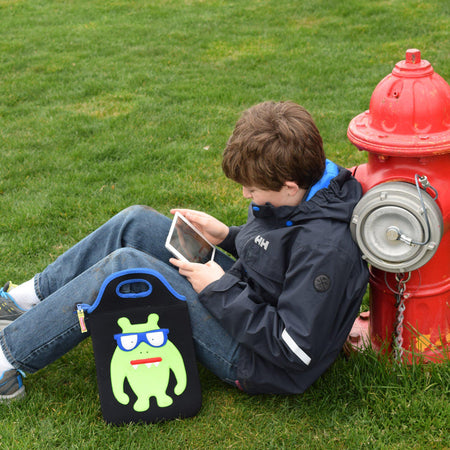Young boy leaning against a hydrant engrossed in his tablet.  The monster geek tablet case by Dabbawalla Bags is resting against his leg.