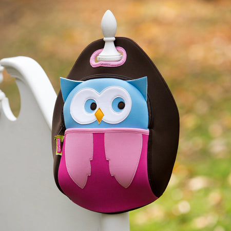 Hoot Owl Lunchbox is hanging on the post of a gate.