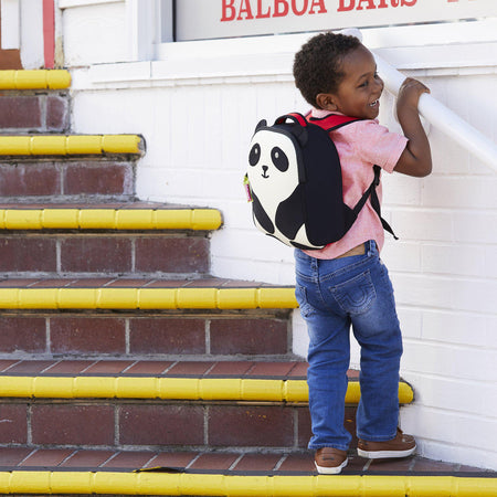 Adorable young boy wearing the panda backpack from Dabbawalla Bags. Off-white front panel  has black eyes, ears and arms stitched on the front.   Mini backpack has attachable leash.