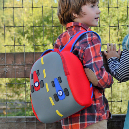 Young boy carrying the sporty Dabbawalla Bags race car backpack