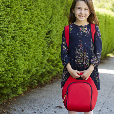 Elementary school girl ready for the first day of school with bright red Dabbawalla washable lunch-bag
