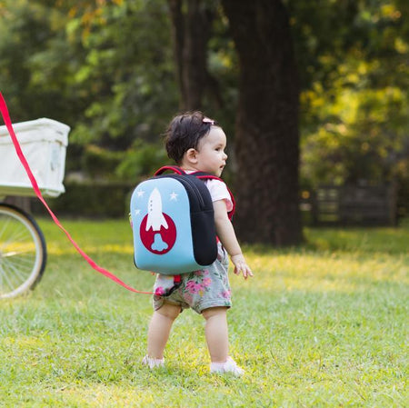 Toddler with Dabbawalla washable rocket harness bag.  Removable tether attaches to the bottom of the harness with a small hook.