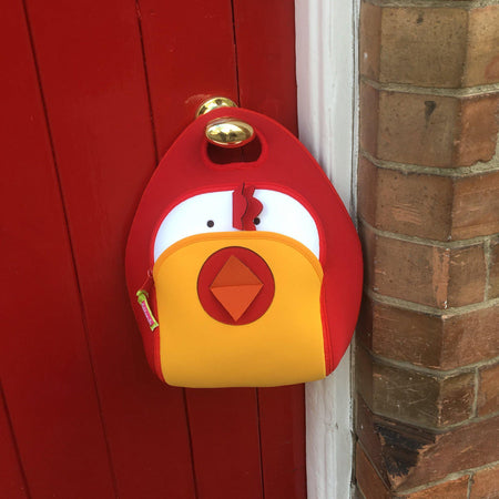 Chicken lunchbox hanging on a red door.  Chicken design is a modern color block design.  Yellow front pocket, red mouth, comb and side panels.  Machine washable and made from sustainable fabrics.