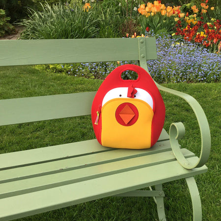 Free Range Chicken Lunch Bag by Dabbawalla Bags placed on a green garden bench in a pretty flower garden.